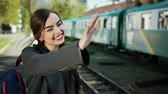 ingázó : One beautiful and happy girl standing in front of the train carriage holds a ticket in her hands and says goodbye to her beloved person and relatives before leaving. On her shoulder is a backpack. Stock mozgókép