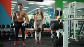 formazione personale : Man and woman flexing arms simultaneously by lifting dumbbells, workout in gym. Both face the camera and poke the muscles. The concept of sport and healthy lifestyle. Athletic bodybuilder look