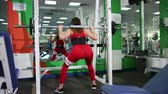 formazione personale : A young beautiful woman raises a bar in the gym and takes a metal pole around the head by squatting. The concept of a healthy lifestyle, a constant keeping yourself in good shape. Fighting overweight Filmati Stock