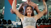 zvýšení : Beautiful woman and a brutal man at gym lifting dumbbell. Gorgeous woman lifting dumbbell with her husband at gym. Sport and healthy lifestyle. Prores, Slow Motion, 4k