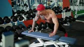 formazione personale : An athletic man in a red cap on his head pushes his seat off, increasing his muscles. Sports activities in the gym, the concept of a healthy lifestyle. Prores, Slow Motion, 4k