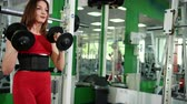 uitdagingen : Veautiful of girl in a red sports suit holds two dumbbells in hand does forward and back squatting. Close-up, Prores, Slow Motion. Increase in muscles legs and hands