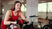 модель : Beautiful young woman with sexual ass twists bicycle pedals in gym. Dressed in red sports suit. And she leaned her hands on bicycle knobs. concert of healthy lifestyle. Close-up, Prores, Slow Motion Стоковые видеозаписи