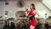 wanten : Beautiful young woman in red suit is drinking water after lesson to quench thirst. In background, training bikes. Concept of a healthy lifestyle, bodybuilding, fitness. Wide angle, Prores, Slow Motion