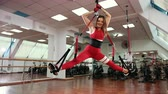 duro : Young beautiful woman doing stretching exercise in gym. The girl hangs in the air, bursting over the ropes. Dressed in a red sport suit. Wide angle, Prores, Slow Motion