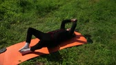 meditare : Elderly woman lying on a mat for yoga, folded her arms and legs and move them up and down. Orange colored carpet. Background of green grass. A hot sunny summer day. Slow motion, prores, wide angle