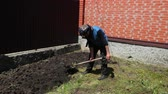 ziegel : the older man, in a blue jacket, black pants, a rag on his head, digging up the ground with a shovel, near a high brick fence, in the afternoon in Sunny weather, slow shooting Videos