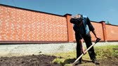 ziegel : an elderly man in a blue jacket, black trousers, with a rag on his head, digging with a shovel, near a high fence, in the afternoon in Sunny weather with a beautiful blue sky, slow shooting