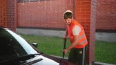 внешний : a man worker with a beard in a white t-shirt and an orange jacket with a smile on his face washes a dark car. car wash using high pressure water jet. splashes of water scatter in different directions