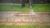pave : a man, sportswear, cleans near the house, washes cobblestones, uses a car wash with high pressure water jets. dirt flies in different directions. in the daytime. close up