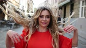 veren : pretty girl, blonde, in a red elegant dress, with gorgeous hair and makeup, crown on his head, vigorously walking down the street, smiling, throwing curls, slow shooting, close-up