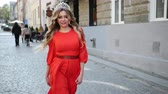 veren : pretty girl, blonde, in a red elegant dress, with gorgeous hair and makeup, crown on his head, energichno walking down the street, smiling, blowing a light breeze, slow shooting, close-up Stok Video