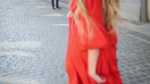 veren : beautiful girl, blonde, in a red elegant dress, with gorgeous hair and makeup, crown on her head, vigorously walking down the street, smiling, circling in front of the camera, slow shooting, close-up Stok Video