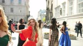 bright clothes : a lot of beautiful, spectacular, girls dressed in exquisite dresses, different colors and crowns, with hairstyles, and great makeup. smiling, dancing in the middle of the street, on a Sunny day