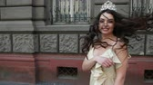 juffrouw : model, brunette, in a light long dress with a deep neckline, long hair and bright makeup, crown on his head, posing and smiling in front of the camera. takes place on the street near the building