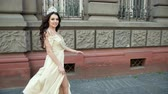 juffrouw : charming girl, model, brunette, in light long dress with a deep neckline, with bright makeup, crown on her head, posing and smiling in front of the camera. photo shoot on the street near the building