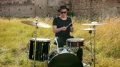 hand drum : a young man, a drummer musician dressed in black clothes, glasses and a hat, with an earring in his ear, plays vigorously on a drum set outside, on a Sunny day, around a tall green grass, slow motion