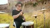 hand drum : professional musician drummer dressed in black clothes, glasses and hat, with an earring in his ear, vigorously playing the drum set on the street, on a Sunny day, around the tall green grass