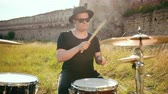 snare : a young man, a drummer musician dressed in black clothes, glasses and a hat, with an earring in his ear, plays vigorously on a drum set outside, on a Sunny day, around a tall green grass, slow motion