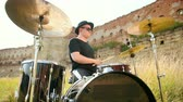 snare : musician drummer dressed in black clothes, hat, with an earring in his ear, rhythmically playing the drum set on the street near the old castle, on a Sunny day, the rays of the sun fall into the frame