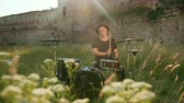 snare : a young man, a drummer musician dressed in black clothes and a hat, with an earring in his ear, plays vigorously on a drum set outside, on a Sunny day, around a tall green grass, slow motion Stock Footage