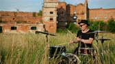 snare : man musician drummer dressed in black clothes, glasses and hat, energetically playing on the drum set, on the street, near the destroyed building on a Sunny day, around tall green grass, slow motion