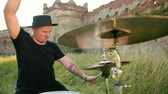 színházi próba : male musician drummer dressed in black clothes, hat, with an earring in his ear, emotionally playing the drum set and cymbals, twists drumsticks, on the street near the destroyed building, slow motion Stock mozgókép