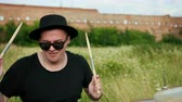 snare : professional musician drummer dressed in black clothes, glasses and hat, with an earring in his ear, vigorously playing the drum set on the street, on a Sunny day, around the tall green grass