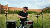 snare : man musician drummer dressed in black clothes, hat, with an earring in his ear, rhythmically playing the drum set and cymbals, throws and twists drumsticks, on street near old castle, on a Sunny day Stock Footage