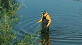 tatlısu : male fisherman in yellow jacket and blue cap special clothes, throws a float, fishing on the river, standing on the shore, on green grass, beautiful nature, in the summer day, Wide angle, slow motion