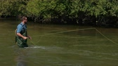 angler : male fisher with a beard and dark hair in special clothes, glasses, throws a float, a man fishing on the river, standing in the water, a small current, the nature is beautiful, summer, slow motion Stock Footage