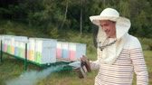 imkerei : man beekeeper in special clothes, holding a smoker to calm bees, a lot of smoke Videos