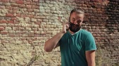 amoroso : Young man with dark hair and beard, blue t-shirt holding smartphone near brick wall talking on the phone, happily and with smile, sunny weather, slow motion, close up