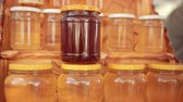 eukaliptus : on wooden shelf there are many jars of honey, two kinds, closed with white and yellow lids, close-up, slow motion