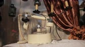 antiquated : on table with knitted tablecloth there is an old white telephone and candlestick with three candles, background is window with tulle and brown curtains, close-up, slow motion