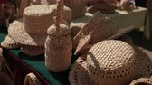 手工芸品 : exhibition of wicker products on street. wicker hats, baskets, handbags, Slippers are on table. handmade products fair, Sunny weather, day, close-up, slow motion 動画素材