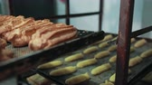 koekenpan : Shelving with different pastry, hand in mitten puts tray above. Already baked eclairs, profiteroles, choux on scratched old pan. Stockvideo