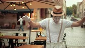 commedia : Handsome young mime in hat, suspenders and white gloves is performing on street in white makeup. Entertainer is walking on straight thin line, looking down at it, balancing with half-raised arms. Filmati Stock