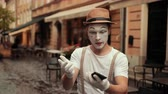 commedia : Handsome young mime points at his phone, talking strictly, then starts arguing. Performer is not satisfied, facial expression shows anger. Show takes place on street near cafe.
