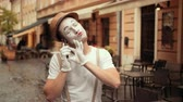 imaginary : Young happy handsome performer of pantomime answers call, flirting, looking satisfied. Mime is smiling while talking, blowing kisses to mobile phone. Performance outdoors near street cafe. Stock Footage