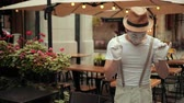 commedia : Handsome young mime in hat, suspenders and white gloves performs near street cafe. Entertainer is jumping forward, happy. Then hesitates to move further, concentrated, jumps, readjusts hat.