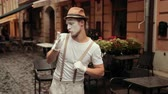 imaginary : Young mime in hat, suspenders and white gloves performs near street cafe. Entertainer greets somebody, smiles, waves hands, flirts with joyful look. Performer walks proudly, blowing kisses.