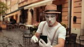 imaginary : Young handsome mime looks at phone, surprised, disoriented. Hits head, becoming normal. Then points at cellphone, shouting, arguing. Street performance near cafe. Stock Footage