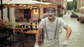 commedia : Young mime in hat, suspenders and white gloves performs near street cafe. Entertainer cant recognize somebody, then recognizes, smiles, waves hands, jumps changing legs with joyful look.