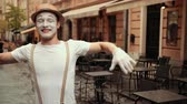 imaginary : Young handsome mime in hat, suspenders and white gloves performs near street cafe. Entertainer greets somebody, smiles, waves hands, flirts with joyful look. Performer shows heart, blowing kisses.
