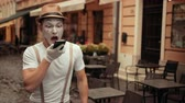 imaginary : Handsome young mime with bored facial expression rolls eyes talking on phone. Performer holding cellphone near ear, then on palm, calling. Entertainer is shouting, arguing while conversation, happy.