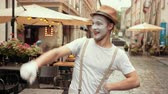 verrast : Young entertainer in hat, suspenders, is performing on street in makeup. Performer is looking left, right greeting people with arms akimbo. Mime in white gloves is smiling, looks happy, joyful.