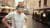imaginary : Young handsome mime in hat, suspenders and white gloves performs on street near cafe. Entertainer looks confident, looking for something outside, searching. Then walks proudly with hands akimbo. Stock Footage