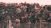 atık : Rusty scrap metal in a heap through a fence Stok Video