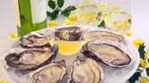 Fresh oysters white plate and lemon and white wine turn table, France Stock Footage